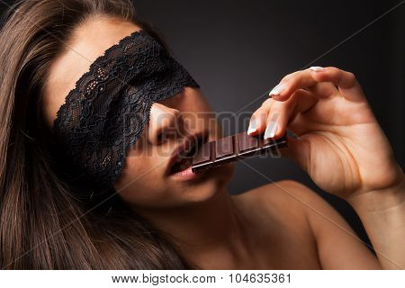 Beautiful woman with blindfold sexy eating chocolate