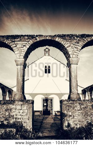 Small catholic Mediterranean church with arch infont, black and white artistic toned photo