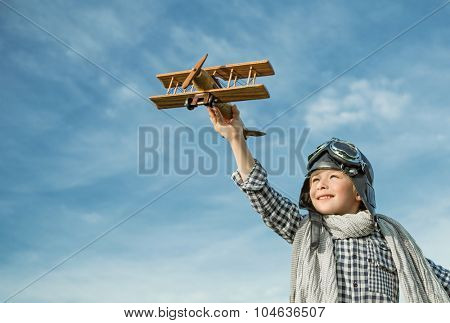 Happy boy with wooden airplane outdoors