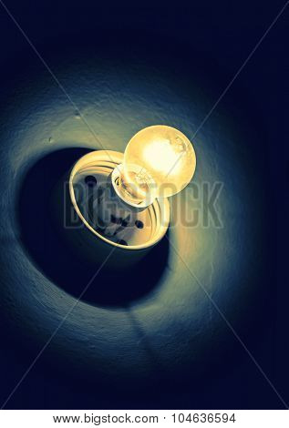 traditional retro  light bulb glowing on grunge textured background artistic toned photo