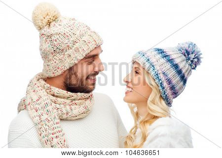 winter, fashion, couple, christmas and people concept - smiling man and woman in hats and scarf