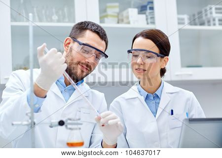 science, chemistry, technology, biology and people concept - young scientists with pipette and test tube making research in clinical laboratory