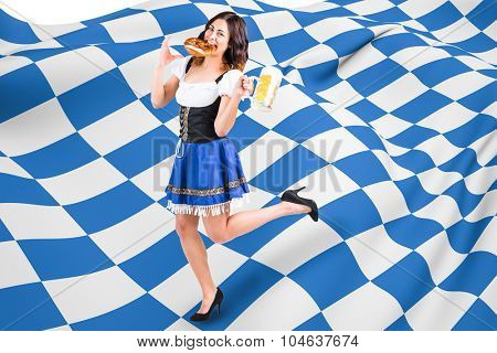 Pretty oktoberfest girl holding beer tankard and pretzel against blue and white flag