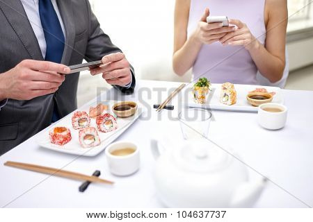 people, leisure, eating, food and technology concept - close up of couple with smartphones taking picture of sushi at restaurant