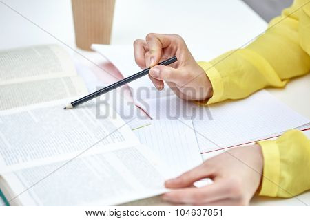 people and education concept - close up of female hands pointing pencil to book or textbook at school