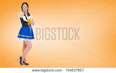 Pretty oktoberfest girl holding beer tankard against orange vignette