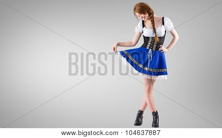 Oktoberfest girl spreading her skirt against grey vignette