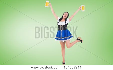 Pretty oktoberfest girl holding beer tankards against green vignette