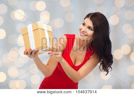 people, holidays, christmas, birthday and celebration concept - beautiful sexy woman in red dress with gift box over holidays lights background