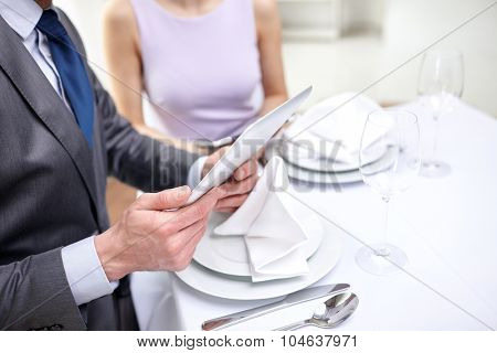technology, people, food and holiday concept - close up of couple with menus on tablet pc computers at restaurant