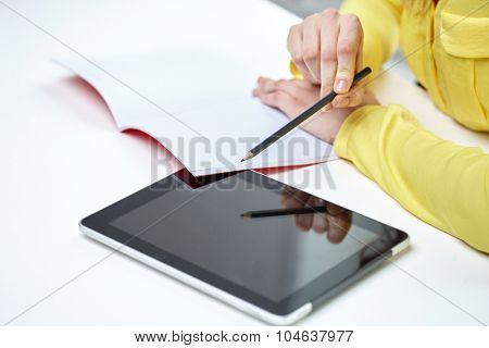 people, technology and education concept - close up of female hands with tablet pc computer and notebook at school