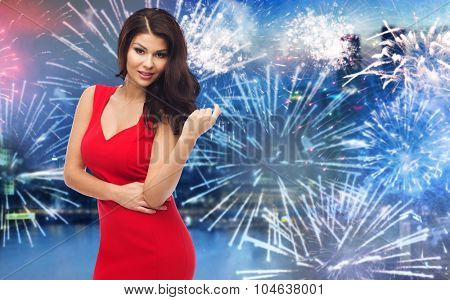 people, holidays, new year and party concept - beautiful sexy woman in red dress over firework lights and night city background