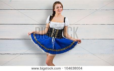 Oktoberfest girl spreading her skirt against painted blue wooden planks