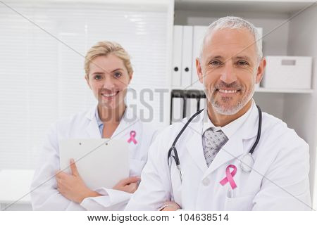 Pink breast cancer awareness ribbon against smiling doctors coworker standing