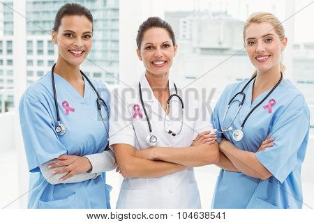 Pink breast cancer awareness ribbon against portrait of female doctors with arms crossed