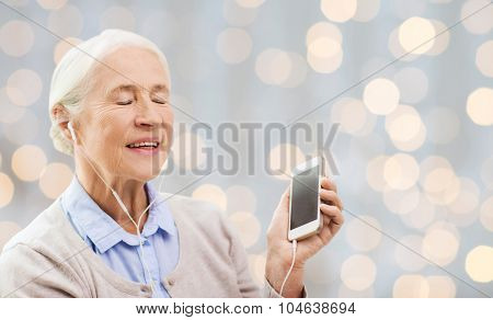 technology, age and people concept - happy senior woman with smartphone and earphones listening to music over holidays lights background