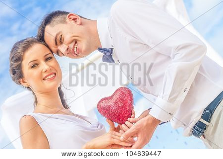 bride and groom holding red heart as symbol of love, outdoor portrait