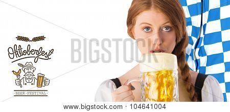 Oktoberfest girl drinking jug of beer against oktoberfest graphics