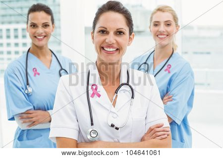Pink breast cancer awareness ribbon against portrait of confident female doctors with arms crossed