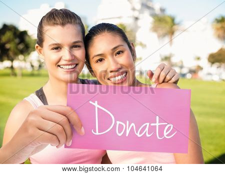 The word donate and hand holding card against two smiling women wearing pink for breast cancer
