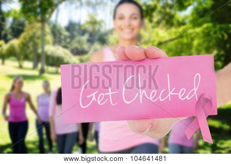 The word get checked and young woman holding blank card against smiling women in pink for breast cancer awareness