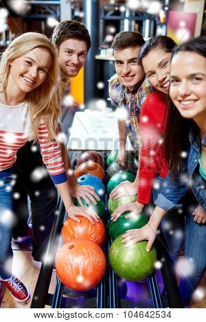 people, leisure, sport, friendship and entertainment concept - happy friends in bowling club at winter season