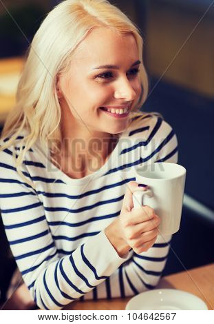 people, leisure, eating and drinking concept - happy young woman drinking tea or coffee at cafe or home
