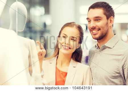 sale, consumerism and people concept - happy young couple pointing finger to shop window in mall