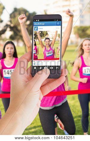 Female hand holding a smartphone against cheering brunette winning breast cancer marathon