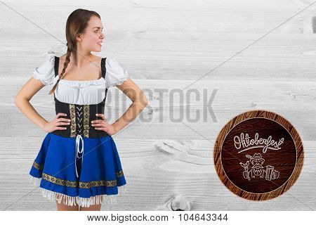 Pretty oktoberfest girl with hands on hips against bleached wooden planks background