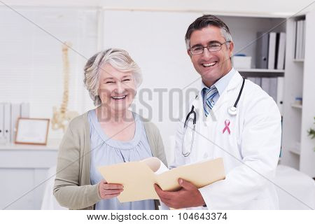 Pink awareness ribbon against happy male doctor and female patient with reports