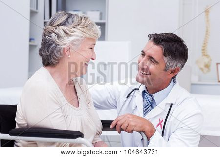 Pink awareness ribbon against male doctor looking at female patient