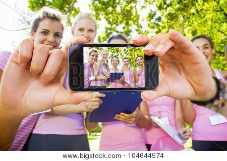 Hand holding smartphone showing against smiling women organising event for breast cancer awareness