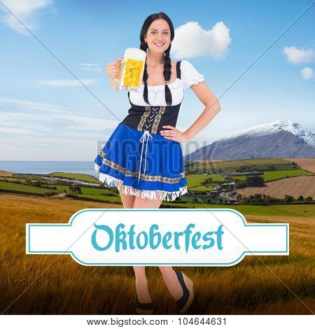 Pretty oktoberfest girl holding beer tankard against country scene with mountain