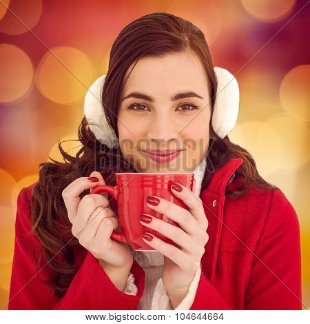 Woman in winter clothes enjoying a hot drink against glowing background