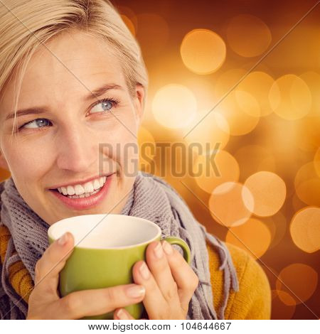 Close up of woman drinking from a cup against glowing background