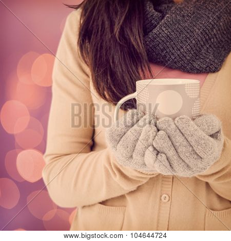 Woman holding polka dotted mug against glowing background