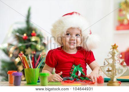 child girl in Santa hat making christmas decoration of plasticine