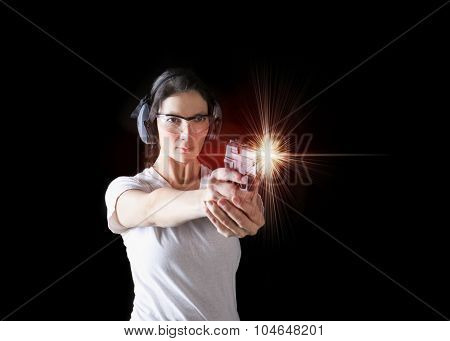 Woman firing a gun with protective gear