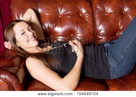 Young woman relaxing on a couch with headphones