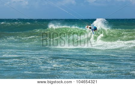 Summer sport water activity background - male kite surfer on high wave