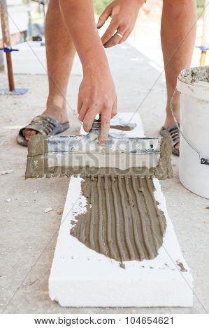 Construction worker puts a gypsum on styrofoam with spatula