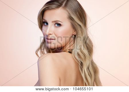 Young smiling blond lady on beige background