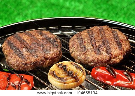 Bbq Burgers Cooked On Hot Charcoal Grill With Vegetables