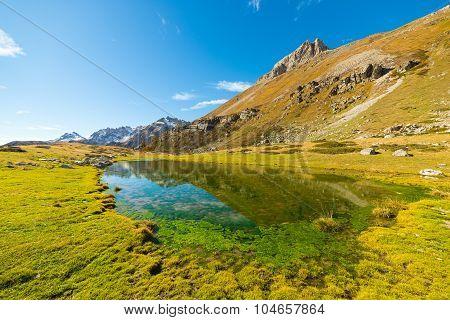 High Altitude Green Alpine Lake In Autumn Season
