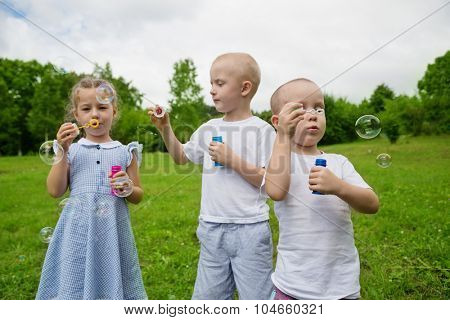 Brothers and sister blowing soap bubbles in park