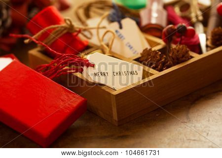 Christmas preparation. Wooden tray with ribbons, Christmas tags, on an old wooden table with vintage feel. Intentionally shot with warm incandescent type lighting and shallow depth of field.