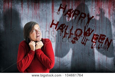 Happy Halloween Sprayed On Wall Next To Scared Woman