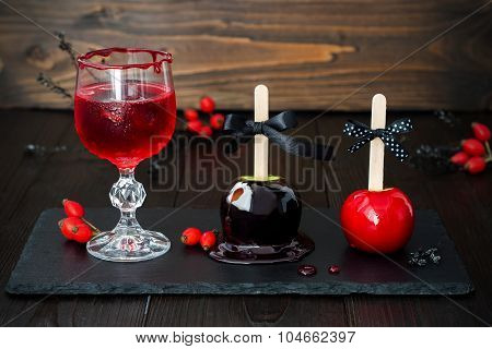 Red bloody vampire cocktail and black poison and red caramel apples. Traditional dessert recipe for