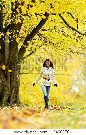 Smiling woman walking in park at autumn season